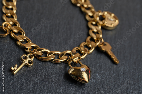 Golden bracelet with keys and a heart on a stone background. Wallpaper Mural