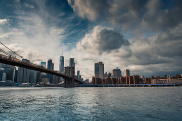 Scenic view of Brooklyn Bridge crossing to Manhattan at Sunset. Dramatic Sky