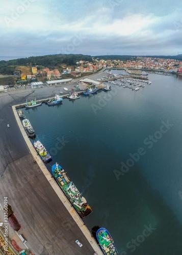Fototapeta Vertical shot of boats on the water under a cloudy sky in Galicia, Spain obraz na płótnie