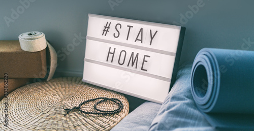Fotografía Coronavirus Yoga at home sign lightbox with text hashtag #STAYHOME glowing in light with exercise mat, cork blocks, strap meditation pillows
