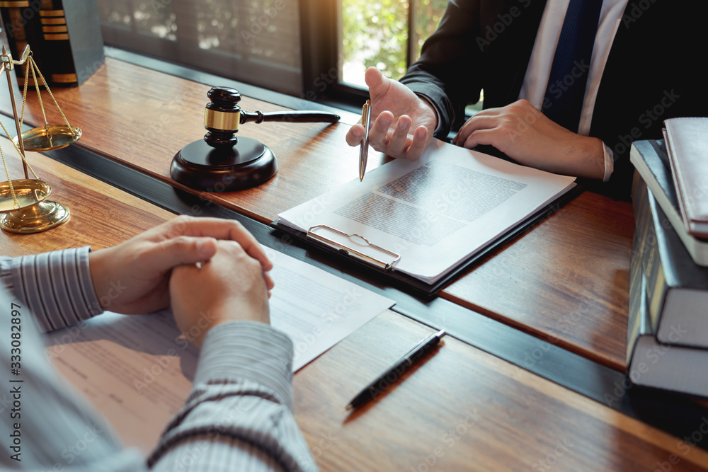 Fototapeta Lawyer working with client discussing contract papers with brass scale about legal legislation in courtroom, consulting to help their customer.