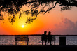 canvas print picture - Silhouettes of man and woman sitting on a park bench overlooking the beautiful ocean sunset. Florida nature. Spring or summer vacations.