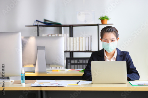 Fotomural Female employee wearing medical face mask while working alone because of new nor