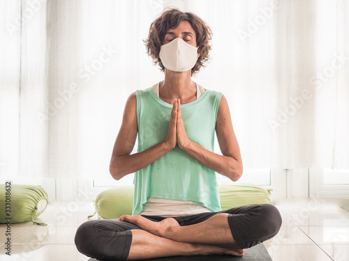 Obraz meditating woman wearing a medical face mask to protect from corona virus covid-19 in crossed legged lotus and praying namaste position on a yoga mat in a studio - fototapety do salonu