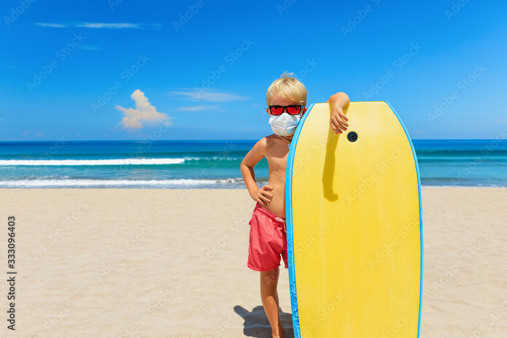 Fototapeta Young surfer wearing sunglasses, protective mask on sea beach with body board. Summer tours, cruises cancellation due to coronavirus COVID-19 epidemic. Safe travel destinations for family vacation.