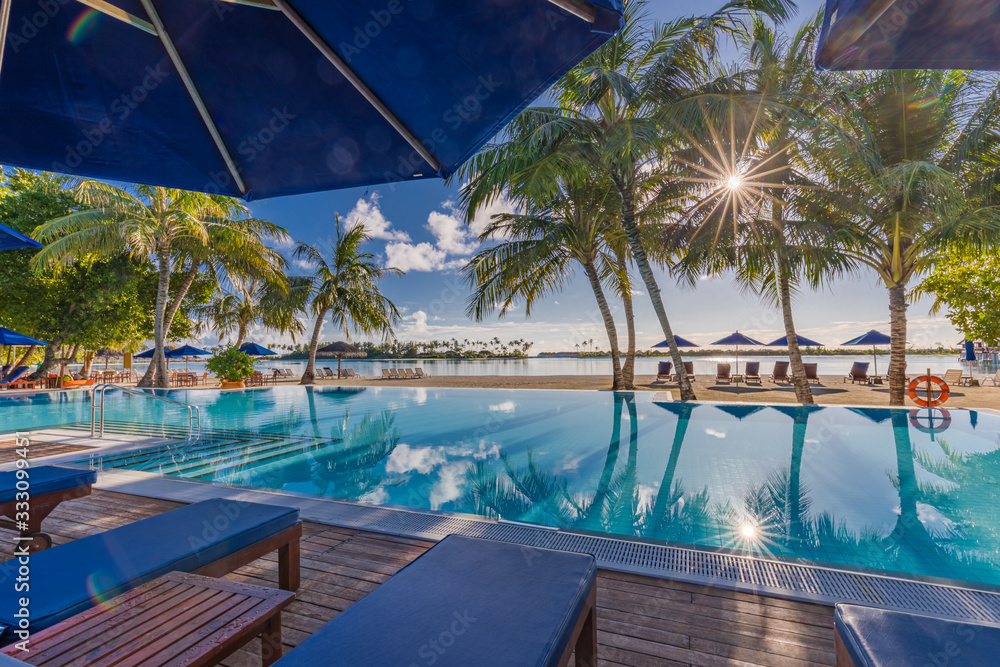 Fototapeta Outdoor tourism landscape. Luxurious beach resort with swimming pool and beach chairs or loungers under umbrellas with palm trees, sun rays, sky. Summer travel and vacation background concept