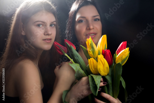Photo Portrait of girl and woman, mother and daughter, in a black one-shoulder dress o