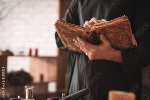 Photo Male alchemist with spell book in laboratory, closeup