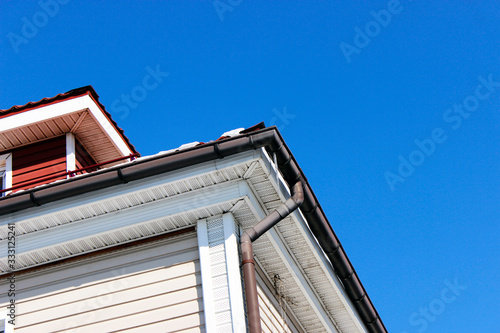 Fototapeta Exterior corner of a house with a roof, a rain gutter and a drainpipe for draining rainwater