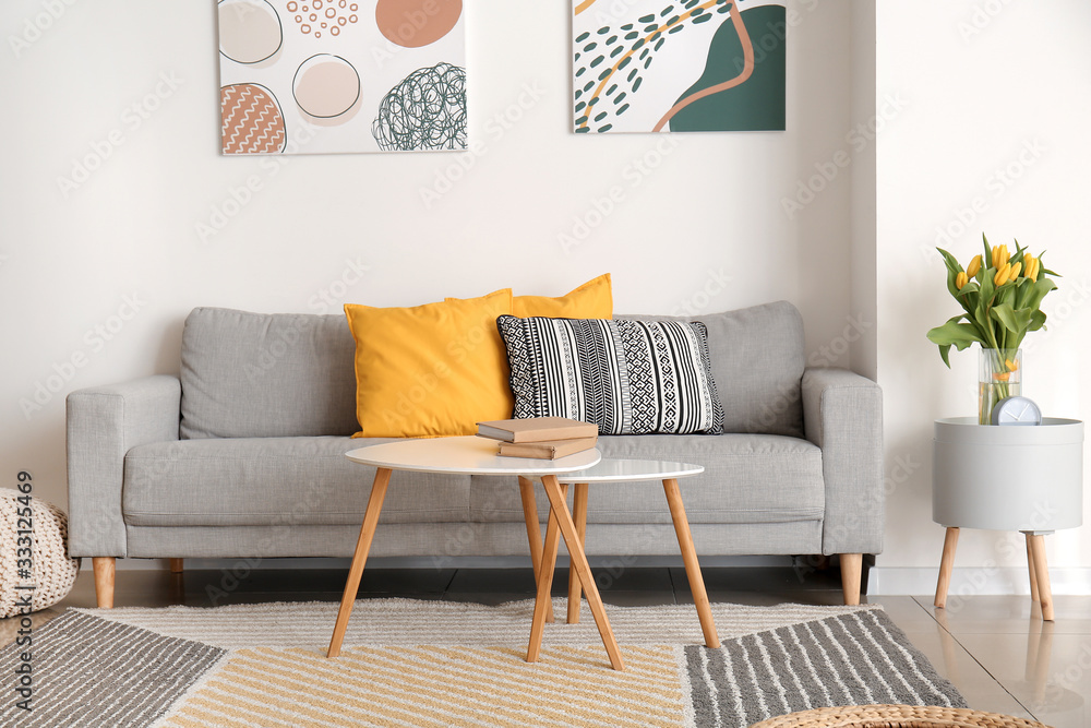 Fototapeta Interior of modern room with comfortable sofa and table with spring flowers