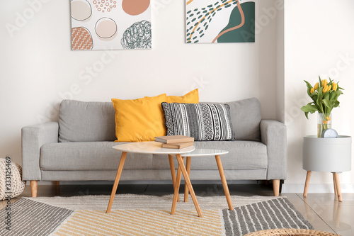Obraz Interior of modern room with comfortable sofa and table with spring flowers - fototapety do salonu