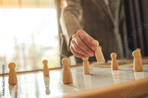 Obraz na plátně Businesswoman leader choosing wooden people from a group of employees on a plann