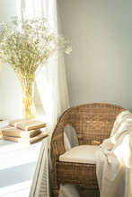 Cozy Reading Nook By The Window With Rattan Wicker Chair, Delicate White Gypsophila Flowers, Opened Book And Window Light And Shadows. Modern Comfortable Living Room Space. Slow Living Concept.