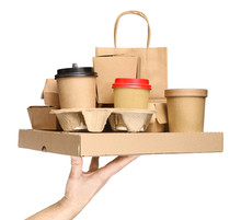 Hand Holding Various Take-out Food Containers, Pizza Box, Coffee Cups In Holder And Paper Bag Isolated On White. Food Delivery Service