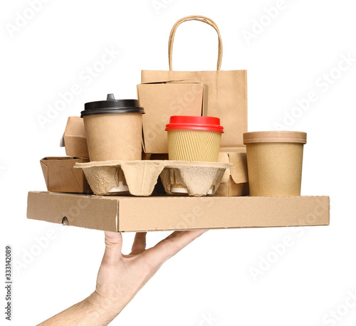 Hand holding various take-out food containers, pizza box, coffee cups in holder and paper bag isolated on white Fototapete