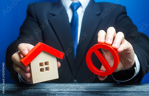 Fotografija A man holds a house and the red prohibition symbol NO