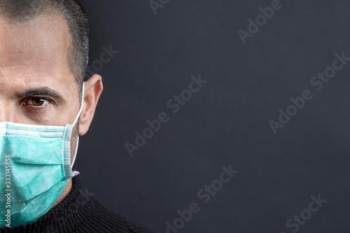 Cuadros en Lienzo Ritratto stretto di  un uomo che  indossa una mascherina chirurgica verde, isola