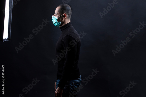 Obraz na plátně Mezzo busto laterale di un uomo rasato che  indossa una mascherina chirurgica ve