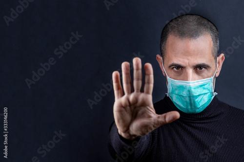 Ragazzo rasato indossa una mascherina chirurgica verde e indica con le mani il s Wallpaper Mural