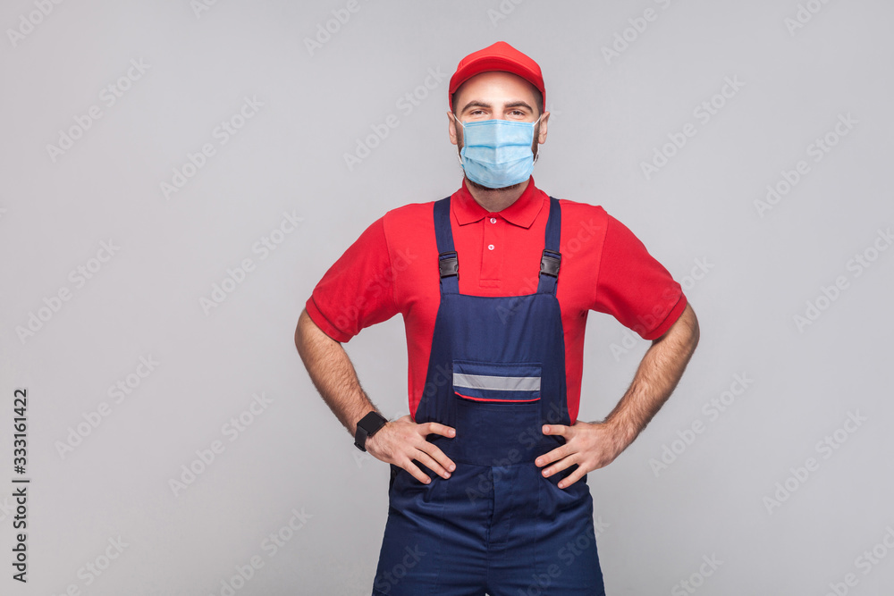 Fototapeta Portrait of young man with surgical medical mask in blue overall, red t-shirt and cap standing and holding hands on waist and looking at camera, indoor, studio shot, isolated on gray background