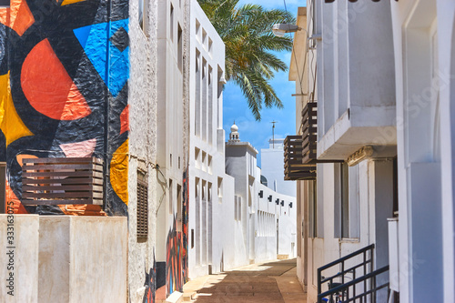 Photo Narrow street with traditional white houses in the old district in Bahrain