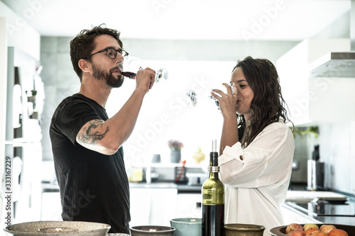Trendy couple drinking wine in kitchen Canvas Print