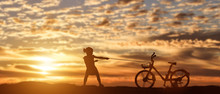 Silhouette Of Girl Pulling Bike At Sunset Background