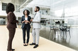 Interracial business team discussing project near office building. Business man and women standing at outdoor glass wall, talking to each other. Corporate communication concept