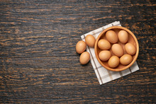 Сhicken Eggs In A Wooden Bowl On A Kitchen Table, Top View.