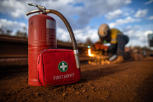Safe Workplace Red First Aid Kit Together With Fire Extinguisher Are Set Ready In Cases Fire Occurs With Defocused Construction Worker Conducting Hot Work Oxy Cutting Steel Plate Structure Background