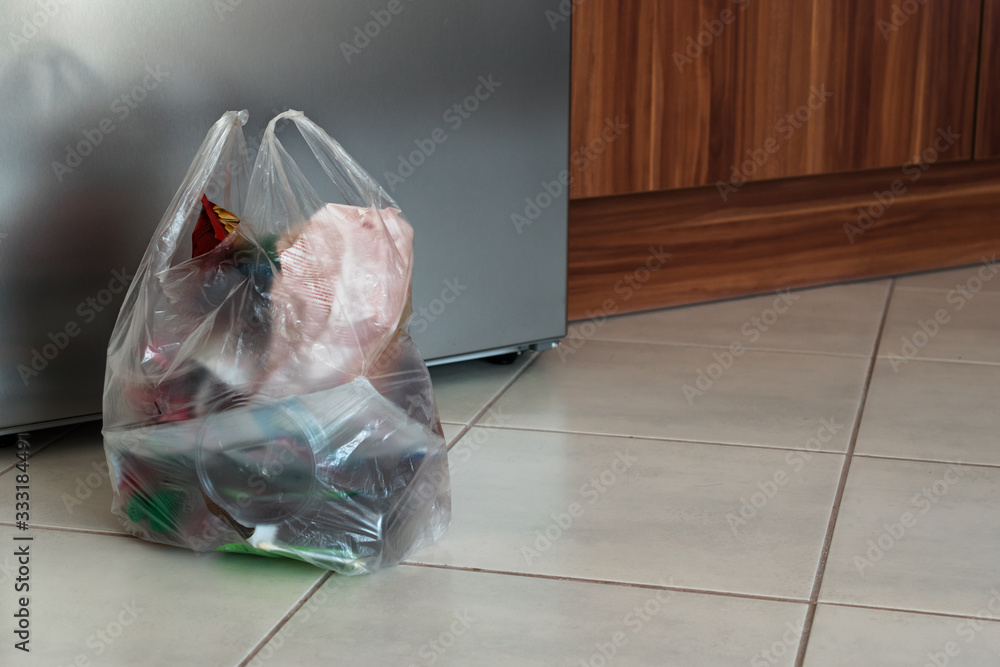 Fototapeta A bag of plastic trash in the kitchen in front of the fridge on the ground.