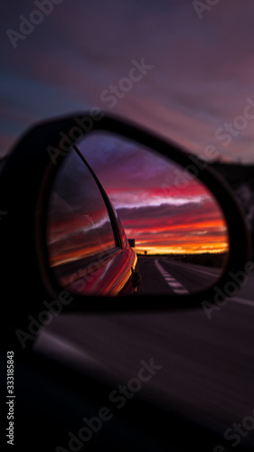 Fotomural Sunset in a car mirror on a long spanish road