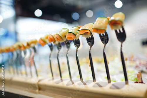 Photo appetizer of cucumber and salmon on a fork close-up on a blured buffet background