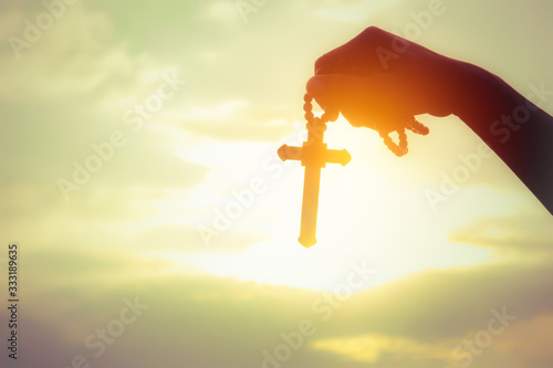 Easter Sunday Celebration Concept : Soft focus silhouette of a young woman with a cross or religious symbol above the sky at sunset to celebrate the resurrection of Jesus Christ Fototapeta