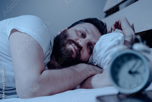 Obraz A lonely bearded man in bed at night suffers from insomnia and he watches the time on the alarm clock. Can not fall asleep, a clock on the pedestal, a bedroom, pajamas, white bedding. - fototapety do salonu