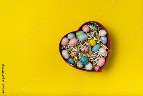 Fototapeta Heart shaped box with colorful Easter eggs. Yellow background. Happy Easter obraz