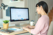 Asian business woman chatting to her colleagues about work plan in chat room. Multiethnic business team using computer for a online meeting. Group of people smart working from home..