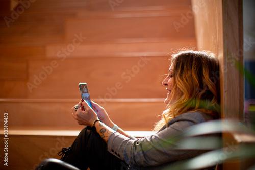 Photo Mujer joven alegre que usa el teléfono móvil sentada en un espacio interior sole