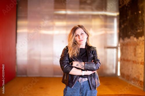 Mujer moderna y alternativa seria rubia con tatuajes de pie con manos cruzadas Wallpaper Mural