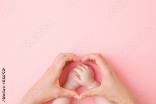 Heart shape created from young mother hands Fototapete