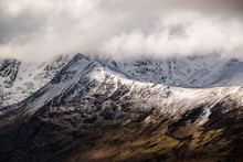 Sun Breaking Through Clouds On A Snow Covered Striding Edge, Lake District, UK