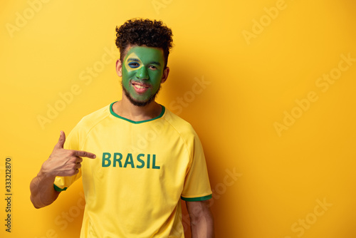 smiling african american football fan with painted face pointing at t-shirt with Canvas