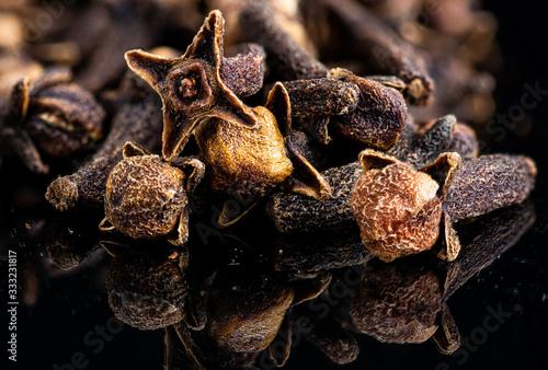 Fototapeta dried cloves spice stacking on a black background obraz