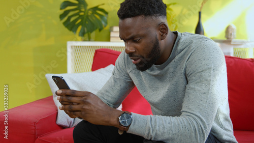 Upset african man receiving bad news on smartphone going crazy of internet deceive covering face in sadness and embarassment Slika na platnu