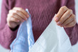 A woman is holding a paper tissue and a cotton handkerchief. Coronavirus advice includes use a disposable paper tissue instead of a cotton one
