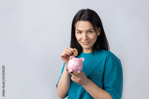 Photo The girl holds a pink piggy bank and a coin in her hands