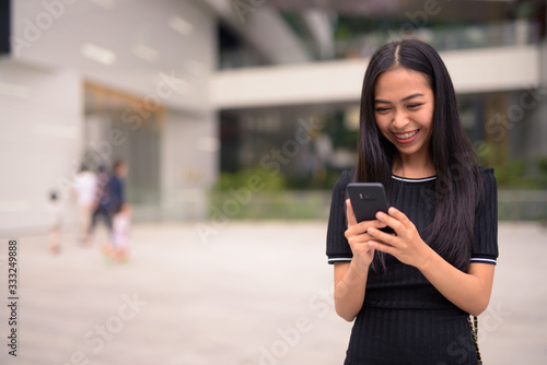 Happy young beautiful Asian tourist woman using phone at the mall outdoors Fototapete