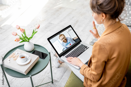 Business woman having a video call with coworker, working online from home at cozy atmosphere