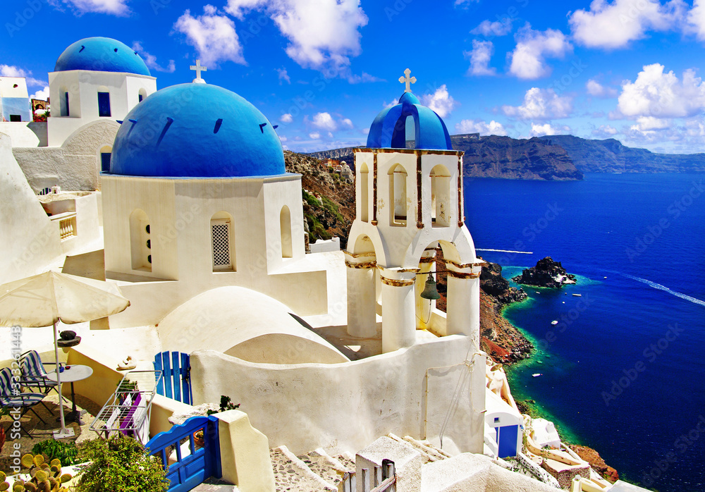 Fototapeta Iconic Santorini - most beautiful island in Europe. view with traditional churches in Oia village. Greece