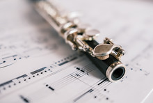 Close Up And Selective Focus On A Classic Wooden Flute On A Background Of Unidentifiable Sheet Music